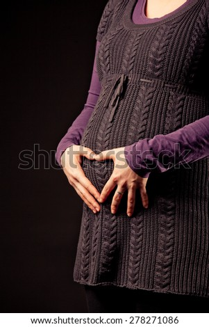 beautiful pregnant young woman show heart with her hands - stock photo
