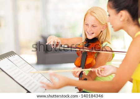 beautiful preteen girl in music class with music teacher - stock photo