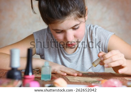 beautiful preteen girl make manicure with black nail enamel