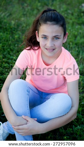 Beautiful preteen girl with blue eyes sitting on the grass - stock photo