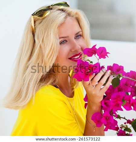 Beautiful  pretty  blonde woman  with pink full lips posing near perfect flowers sniffs it  and enjoy their fragrance .Wearing sunglasses  and yellow dress. - stock photo