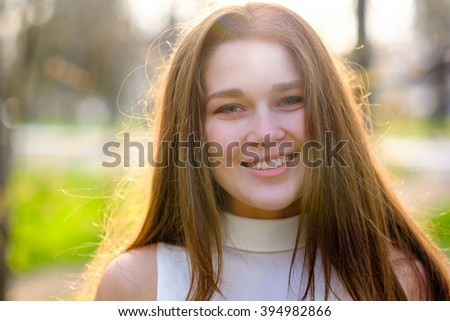 Beautiful, pretty student, teenage girl with long hair in the park on a sunny day. Closeup portrait of a young attractive, smiling, happy woman outdoors. Spring or autumn day outside on the nature. - stock photo