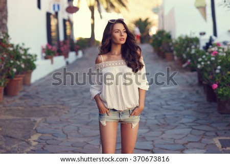 Beautiful pretty woman walking at old town pavement street and looking away. Travel concept - stock photo
