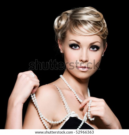 Beautiful pretty woman with pearls on her neck - black background - stock photo