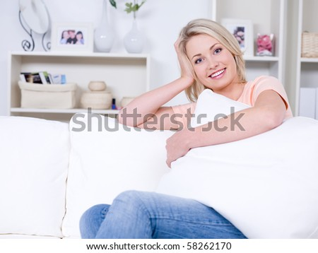 Beautiful pretty young woman relaxing on the sofa in the comfortable room - stock photo
