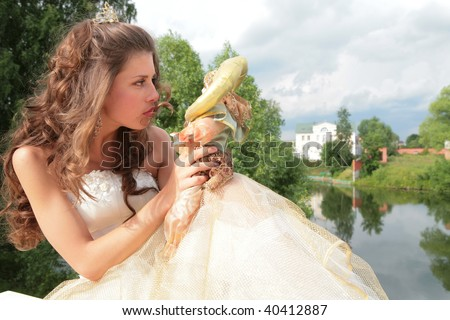 beautiful princess in golden dress looks at loved doll - stock photo