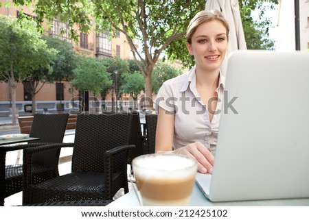 Beautiful professional young business woman sitting at a coffee shop drinking a beverage and using laptop computer in the financial city, smiling outdoors. Business people at work.
