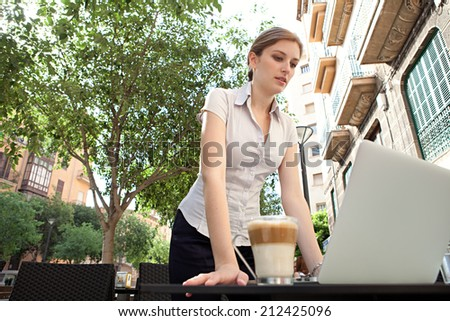 Beautiful professional young business woman standing at a coffee shop table, drinking a beverage and using laptop computer working in the financial city, outdoors. Business people at work.