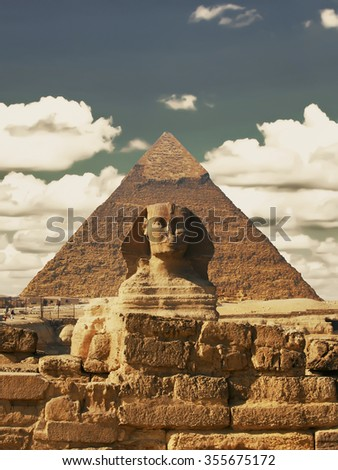 Beautiful profile of the Great Sphinx including pyramids of Menkaure and Khafre in the background on a clear sunny, blue sky day in Giza, Cairo, Egypt. Pyramid Egyptian Sphinx on background of clouds - stock photo