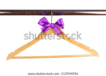 Beautiful purple bow hanging on wooden hanger isolated on white - stock photo