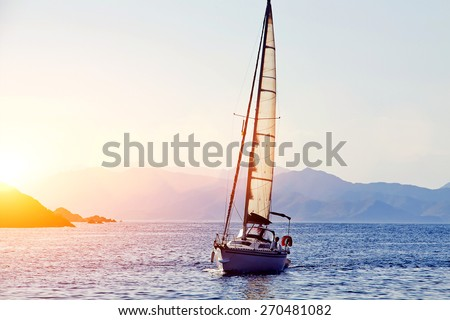 Beautiful racing yacht in the Mediterranean sea with blue sky and mountains on background, sailing boat at gold colorful sunset - stock photo