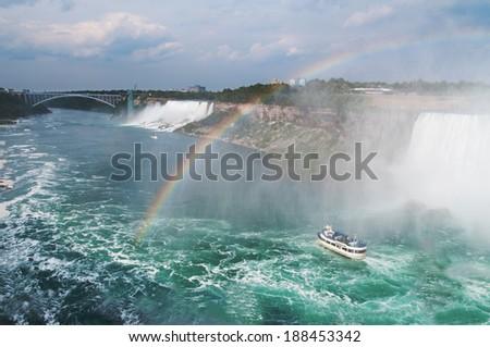 Beautiful rainbow forming near tourist boat at Niagara Falls, Ontario, Canada  - stock photo