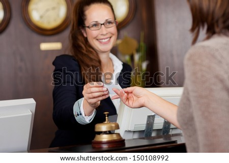 Beautiful receptionist handing over a business card to a customer with a warm welcoming smile - stock photo