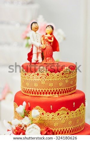 Beautiful red and yellow wedding cake in Indian style with bride and groom figurines on top - stock photo