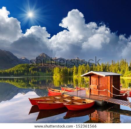 Beautiful red boat in a mountain lake Strbske Pleso, Slovakia, Europe - stock photo