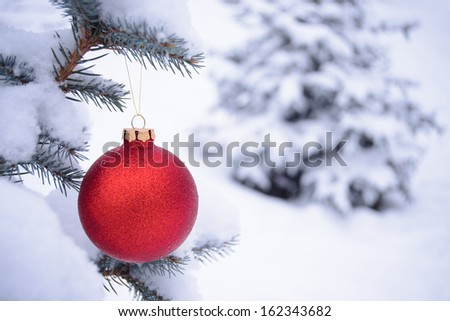 Beautiful Red Christmas Ball on the Fir Branch Covered with Snow. Christmas Background - stock photo