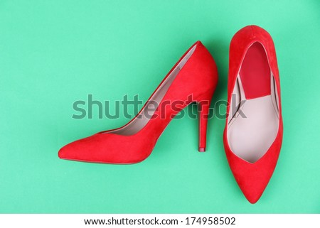 Beautiful red female shoes, on green background - stock photo
