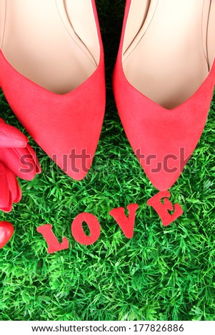Beautiful red female shoes, on green grass background - stock photo