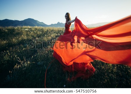 Beautiful red hair bride in a wedding magnificent dress with veil lace in Sunset rays at Crimea, Russia