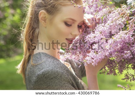 Beautiful red hair ginger slim young woman with fresh skin in casual outfit, posing with flowers. Sunny summer day in park (nature). Daylight