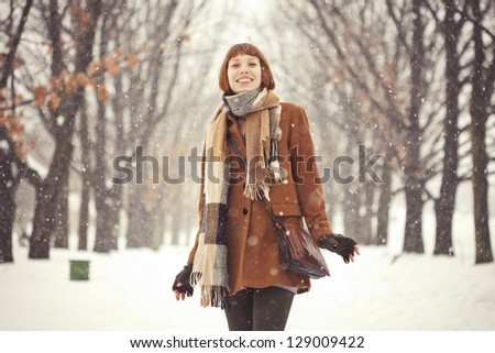 Beautiful red hair girl in winter park with snow