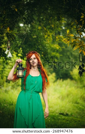 Beautiful red hair girl with deep green eyes holding lantern with candle. Dreamy Magical Portrait.  - stock photo
