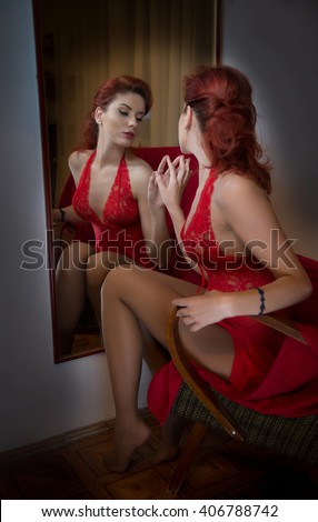 Beautiful red hair girl with long red lace dress posing in front of a large wall mirror. Young attractive redhead, side view with perfect long leg exposed. Sensual elegant woman in red dress - stock photo