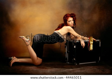 beautiful red hair woman in sexy dress leaned on trunk, studio shot