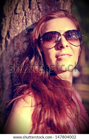 Beautiful red-hair woman in sunglasses on the natural background. Special soft-colored edition. Eyes in focus.