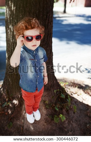 Beautiful red-haired boy with beautiful eyes in a shirt walking on a sunny day with glasses - stock photo