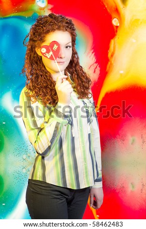 beautiful red haired caucasian girl demonstrating sweet candy with kiss me words standing isolated over colorful abstract background