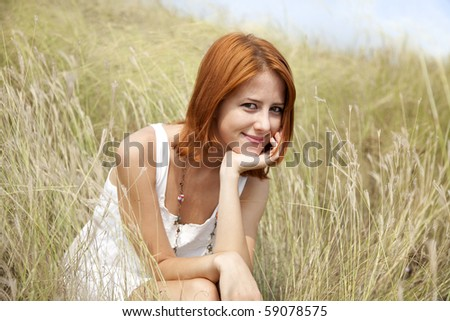 Beautiful red-haired girl at grass. Outdoor photo. - stock photo