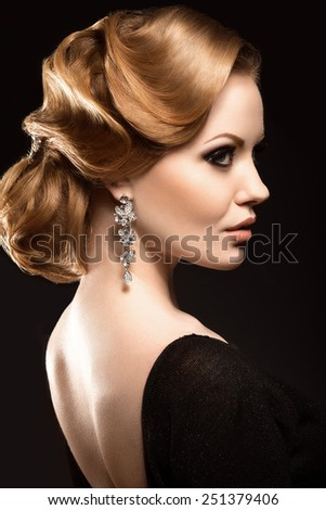 Beautiful red-haired girl in a black dress with a smooth evening haircut in the form of waves and bright makeup. Beauty face. Picture taken in the studio on a black background. - stock photo