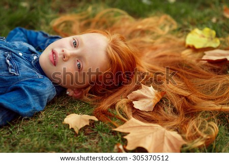 beautiful red-haired girl in the autumn park lying on the grass - stock photo