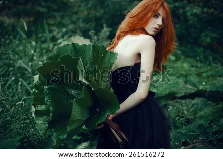 Beautiful red-haired girl posing in the woods with burdock behind her back - stock photo
