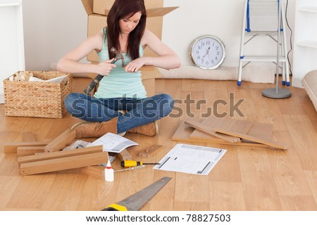 Beautiful red-haired girl using a hammer for diy at home - stock photo