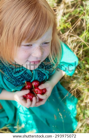 beautiful red-haired girl with a handful of ripe cherry in the hands - stock photo