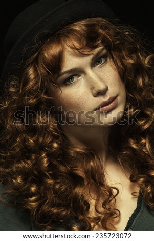 Beautiful red-haired girl with curls, black hat