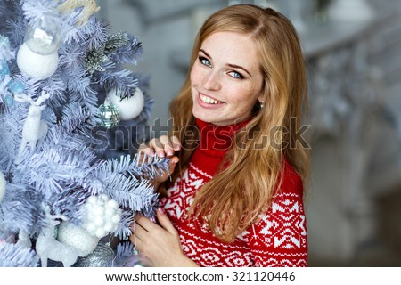 Beautiful red-haired girl with freckles and with blue eyes in a red sweater with white ornaments stands near a tree in the New year and smiles - stock photo