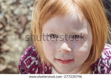 beautiful red-haired little girl with grey eyes cute smiles - stock photo