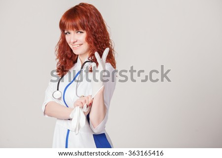 Beautiful red-haired model in a medical gown pulls sterile rubber gloves.