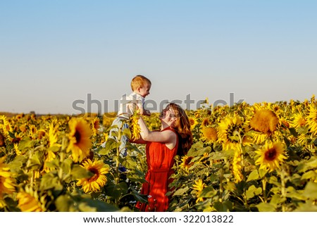 Beautiful red-haired mother is tossing up her cute red-haired little son in sunflower field. Both are happy. Image with selective focus - stock photo