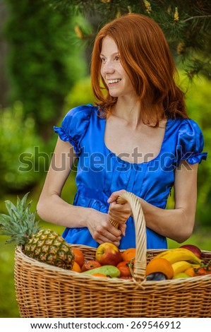 Beautiful red-haired smiling young woman in blue blouse with a fruit basket on the background summer green city park.