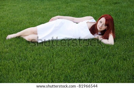 beautiful red haired teen with freckles in grass - stock photo