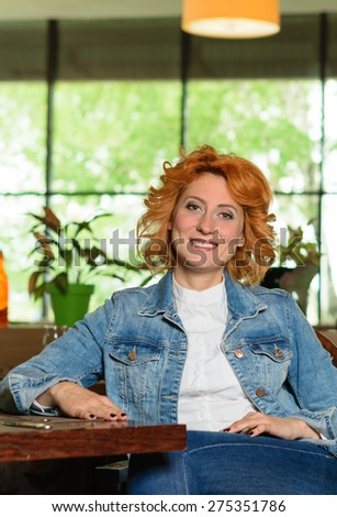 beautiful, red-haired woman sitting in a chair in a restaurant - stock photo