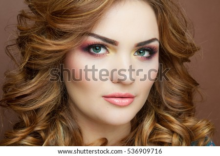 Beautiful red haired woman with stunning colorful make up and with ideal curls, dark background, closeup fashion photo