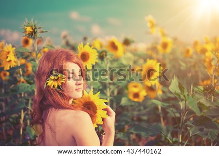 Beautiful red-haired woman with sunflowers. Young model on the background of summer  landscape.