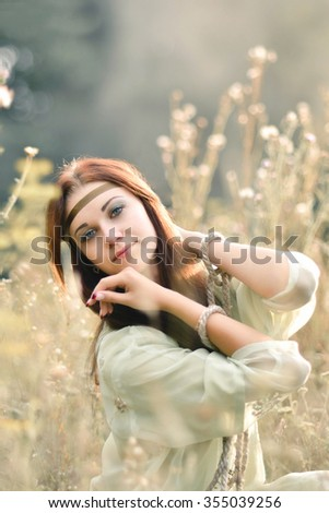 Beautiful,red-haired,young,playful,creative,cute,fun,peaceful,adorable,fashionable,sunny,happy girl in the field with many flowers,tapes,ropes,chains,meadow,nice smile in summertime.Sunset.Sunlight