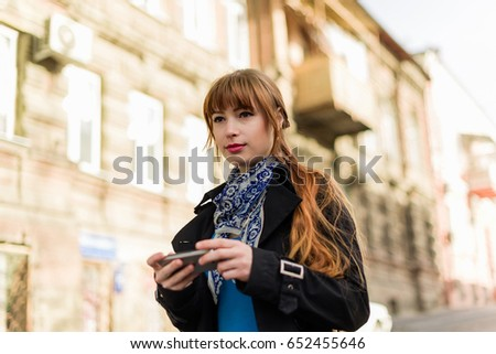 Beautiful red-haired young woman dressed in a stylish coat, walking down the city street on a sunny day, using the Mobile Phone. The concept of people, travel, tourism, communications and lifestyle