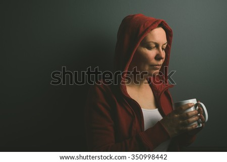 Beautiful red hooded lonely woman drinking cup of coffee in dark room, low key portrait